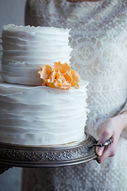 bride holding a tiered wedding cake on vintage silver tray. - orange hochzeitstorten stock-fotos und bilder