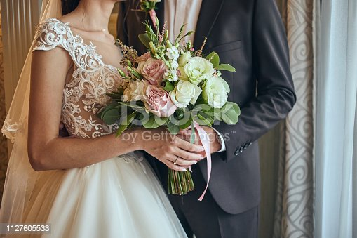 istock Bride holding a wedding bouquet in the hands standing near groom 1127605533