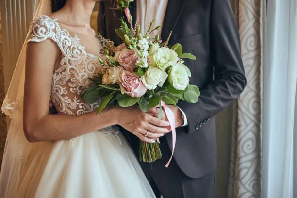 花嫁の新郎の近くに立って手でウェディング ブーケを保持 - 結婚式 ストックフォトと画像