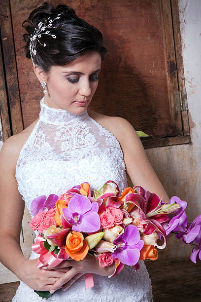 Bride Holding and Looking Bouquet Inside Old Countryhouse - foto de acervo