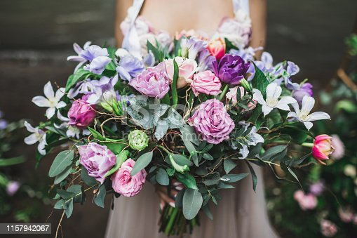 Bride holding b beautiful colorful wedding bouquet of roses, peonies and tulips in bright pink, coral and purple colors.