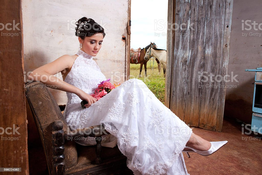 Bride Holding Bouquet and Sitting Inside Old Countryhouse Horses Outside foto royalty-free