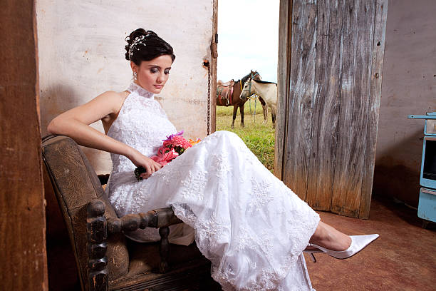 Bride Holding Bouquet and Sitting Inside Old Countryhouse Horses Outside - foto de acervo
