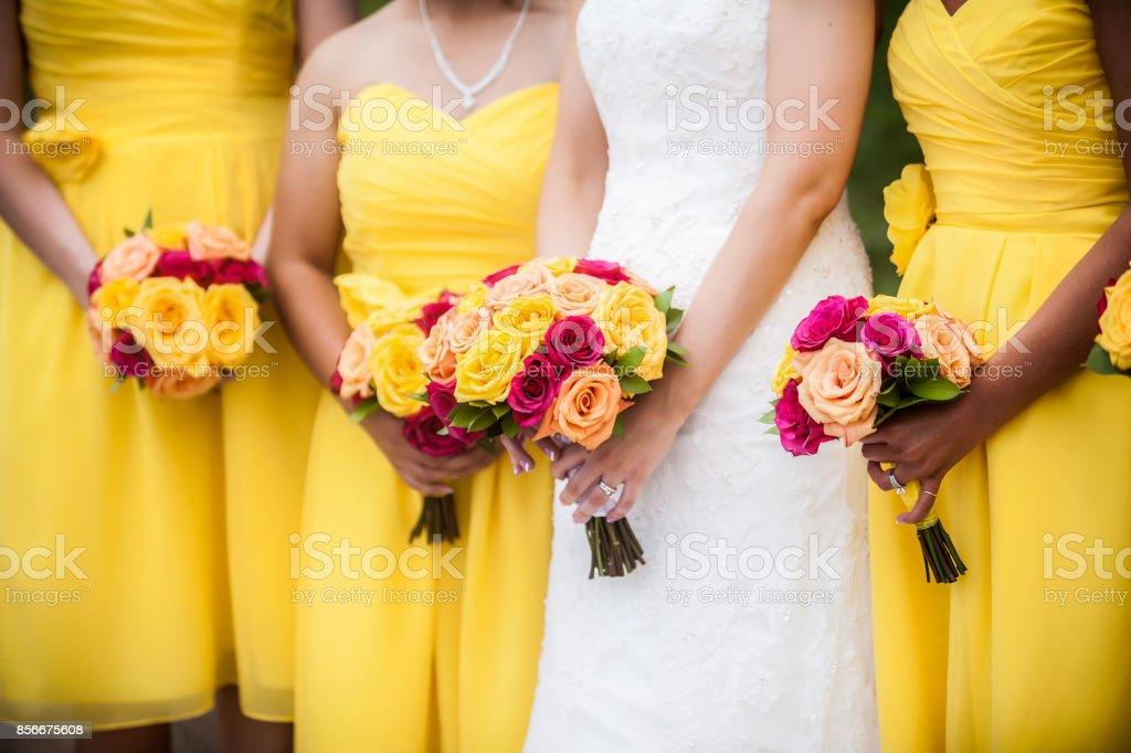 Braut Holding Bouquet mit Brautjungfern im Hintergrund – Foto