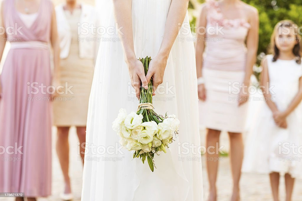 Bride Holding Flower Bouquet With People Standing In Background stock photo