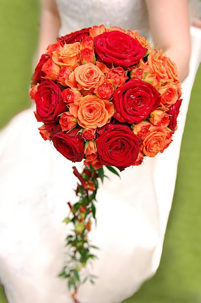 Bride holding orange bouquet stock photo