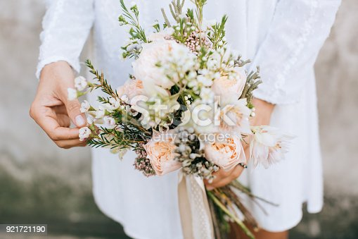 istock Bride holding the wedding bouquet, with beautiful flowers rustic style 921721190