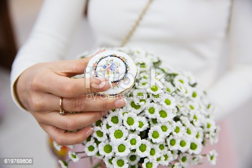 istock Bride holding wedding bouquet and box for rings 619769808