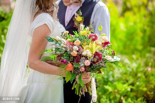 istock Bride holding wildflower bouquet 629431258