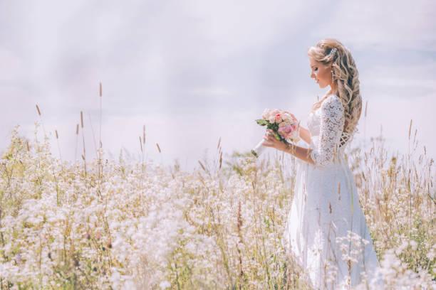 bride holds a delicate wedding bouquet in a field of white flowers. - panna młoda zdjęcia i obrazy z banku zdjęć