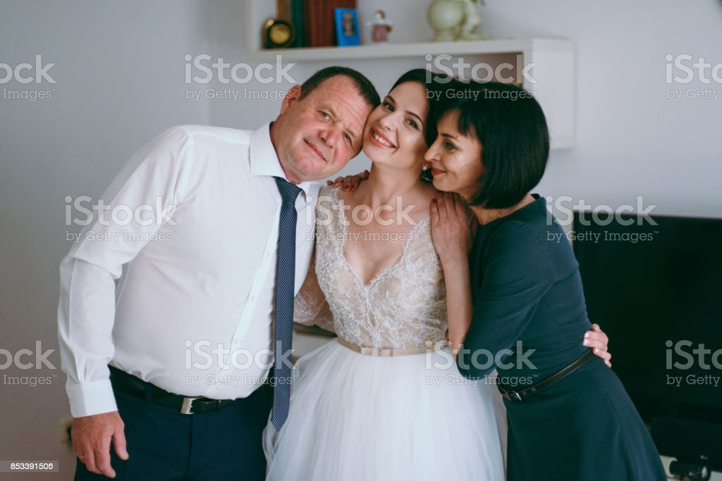 Bride hugging parents mom and dad stock photo