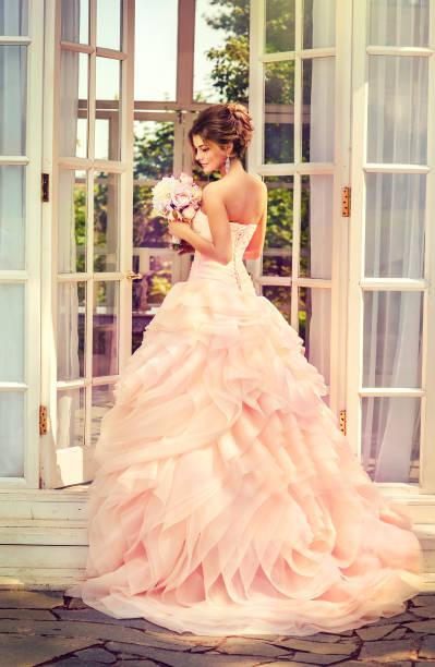braut in einem noblen hochzeitskleid mit brautstrauß. - verlobungskleider stock-fotos und bilder
