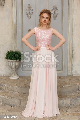 istock Bride in a tender light pink wedding dress in a morning. Fashion beauty full-lenght portrait 1054970060