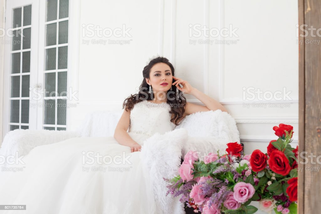 bride in a wedding dress and a crown sits in the white hall stock photo