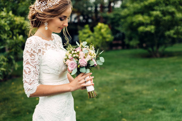 bride in a white long dress with a wedding bouquet is standing alone and looks at a bouquet waiting for her husband stock photo