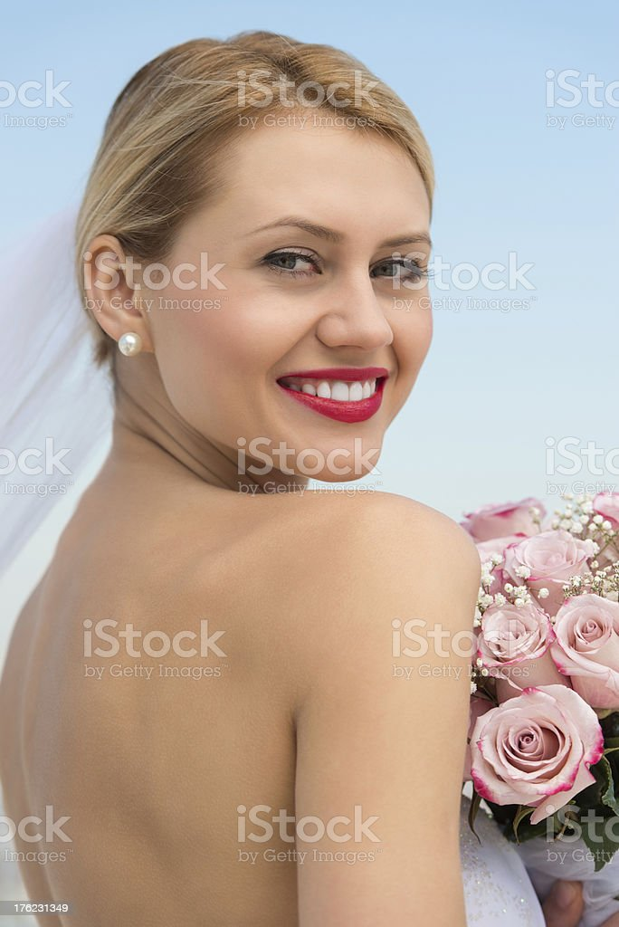 Bride In Backless Dress With Flower Bouquet Against Clear Sky stock photo