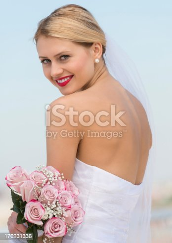 Rear view portrait of beautiful young bride in backless wedding dress holding flower bouquet against sky