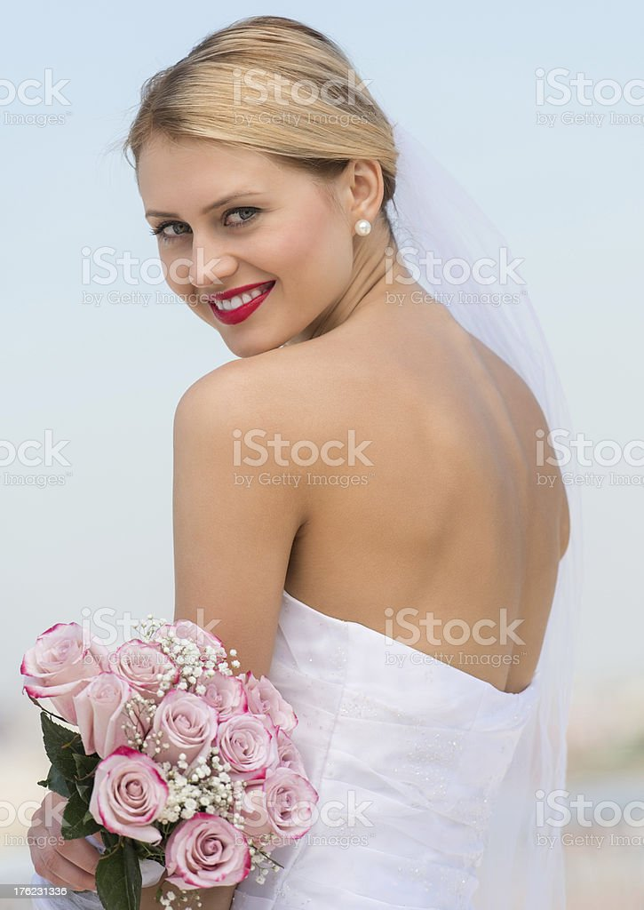 Bride In Backless Wedding Dress Holding Flower Bouquet Against Sky stock photo