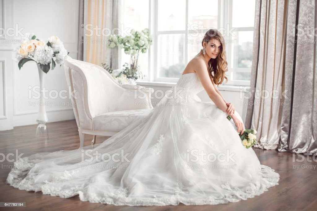 Bride in beautiful dress sitting resting on sofa indoors - foto stock