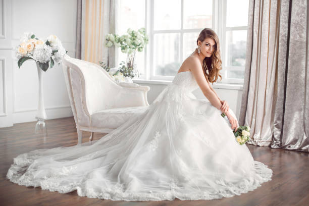 f95711a3a0b Bride in beautiful dress sitting resting on sofa indoors stock photo · Beautiful  white wedding dress stock photo · Happy bride stock photo