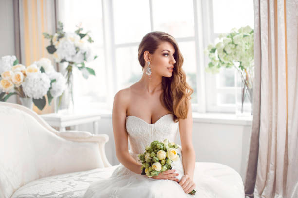 Bride in beautiful dress sitting resting on sofa indoors Wedding. Bride in beautiful dress sitting on sofa indoors in white studio interior like at home. Trendy wedding style shot. Young attractive caucasian brunette model like a bride against big window tender posing. corset stock pictures, royalty-free photos & images