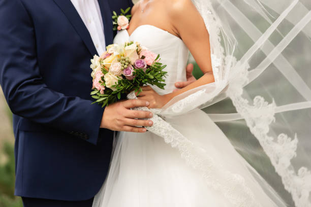Bride in beautiful white wedding dress with bouquet and elegant groom in blue suit at happy wedding day stock photo