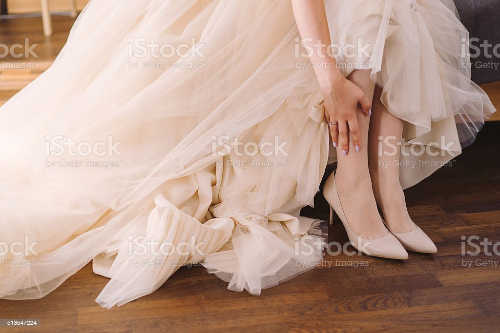 bride in beige wedding dress put on her shoes stock photo
