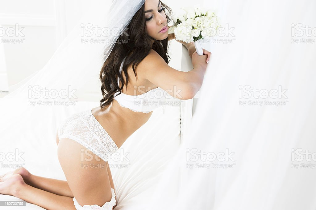 Bride in lingerie kneeling on headboard royalty-free stock photo