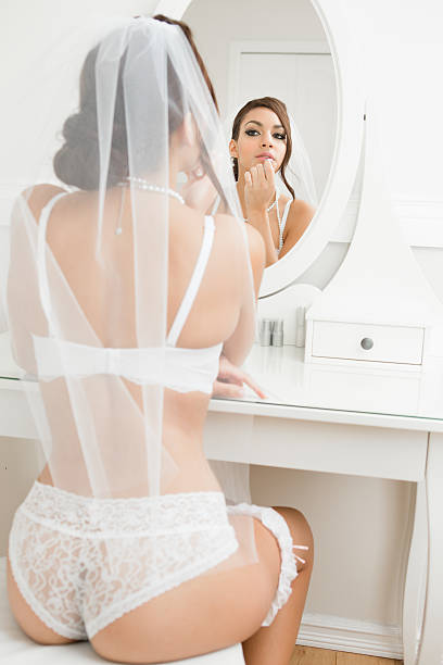 Bride in lingerie putting on lipstick stock photo