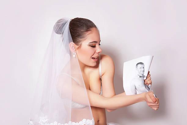 Bride in veil break the groom photo, gray background stock photo