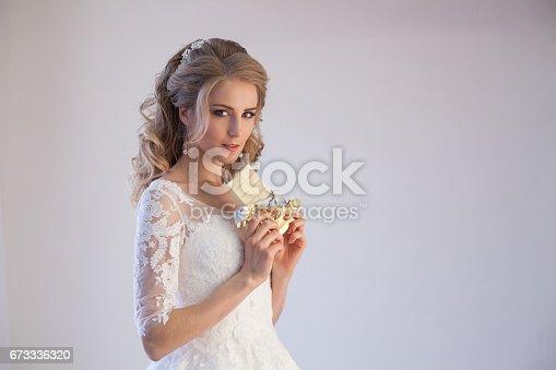 674214372istockphoto bride in wedding dress holding a chocolate 673336320