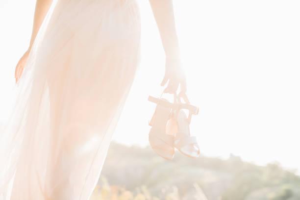 bride in wedding dress holding a shoes at sunset. - goldhochzeitsschuhe stock-fotos und bilder