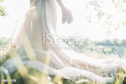 istock Bride in wedding dress holds shoes against sun. fine art photography 698704528