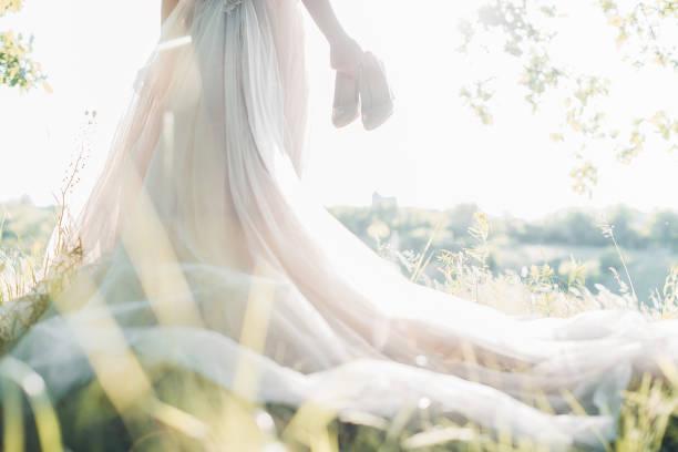 braut im hochzeitskleid hält schuhe gegen die sonne. fine art-fotografie - verlobungskleider stock-fotos und bilder