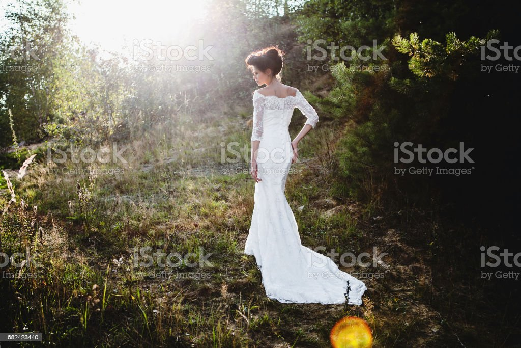bride in wedding dress standing in woods or park royalty-free stock photo