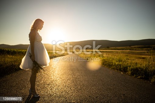 Young beautiful bride in wedding dress standing on countryside road with wildflower bouquet on sunny day