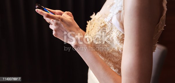 istock Bride in wedding gown using smart mobile phone, Shopping and Communicating with digital technology. Modern Trend, Lifestyle, Business Transaction, Communication, Working online and Mobile App concept 1140076917