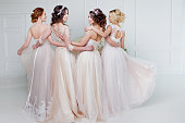 istock Bride in wedding salon. Four beautiful girl are in each other's arms. Back, close-up lace skirts 843339104