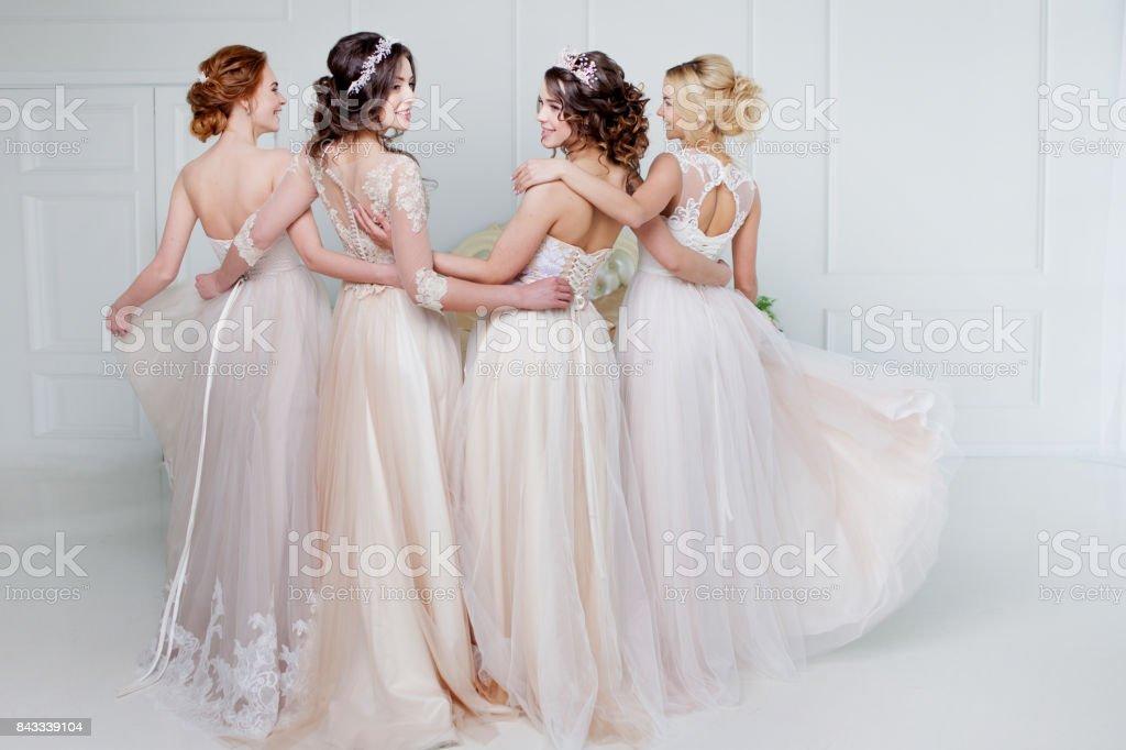 Novia en el salón de la boda. Cuatro hermosa chica están en brazos del otro. Faldas de encaje espalda, primer plano - foto de stock