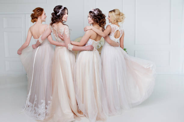 Bride in wedding salon. Four beautiful girl are in each other's arms. Back, close-up lace skirts stock photo