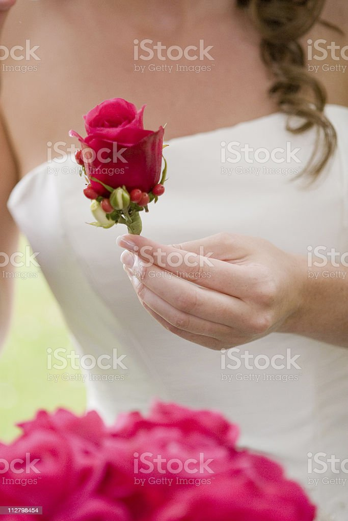 Bride in white dress holding pink flower at wedding royalty-free stock photo