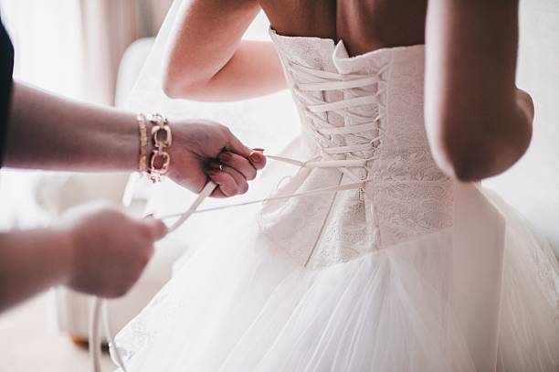Bride in white dress Bridesmaid helping the bride to wear a dress corset stock pictures, royalty-free photos & images