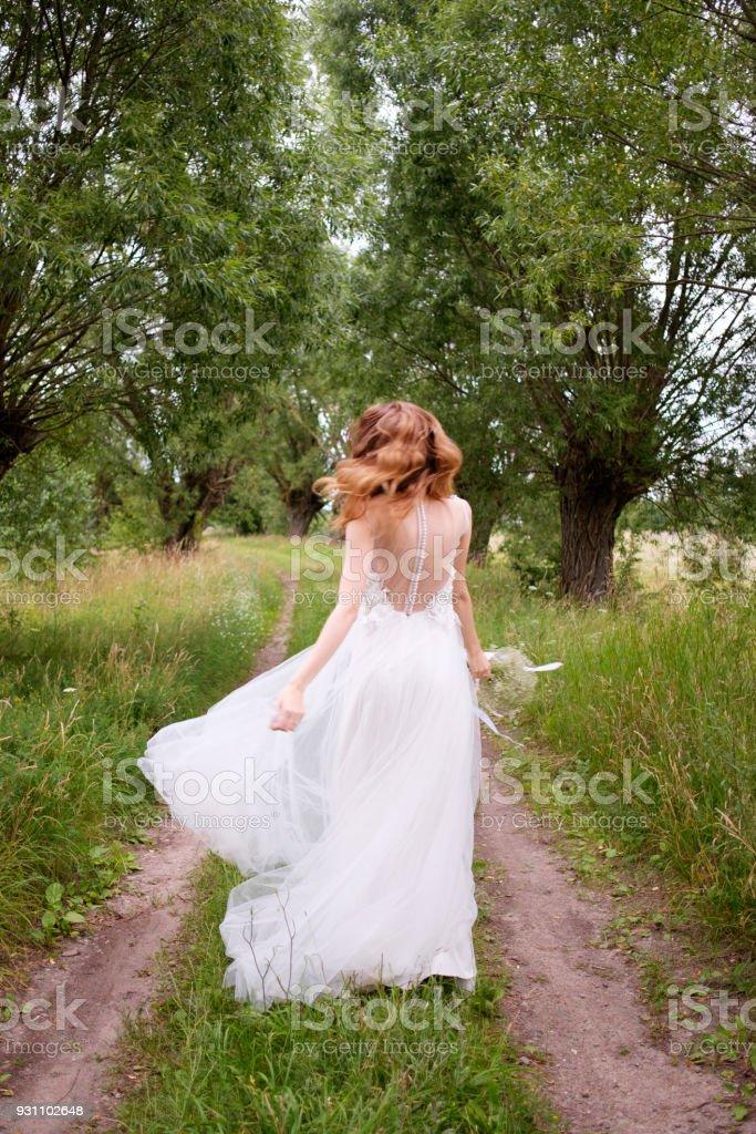 gelin gelin buketi ağaçlar, görünümü şeritte arkadan kaçıyor ile beyaz llight gelinlik - Royalty-free Bahar Stok görsel
