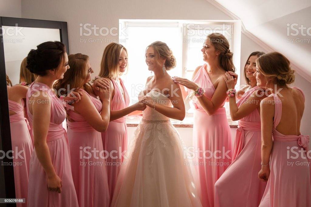 Bride In White Wedding Dress And Bridesmaids In Pink Dresses Posing