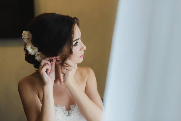 Bride in white wedding dress puts on earring. stock photo
