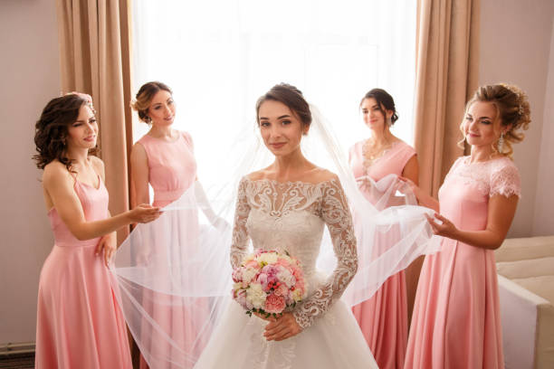 Bride in white wedding dress with long sleeves and bridesmaids in pink dress posing near window before wedding ceremony stock photo