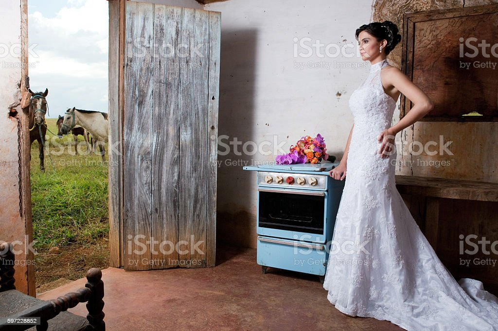 Bride inside old countryhouse kitchen with stove bouquet and horses foto royalty-free