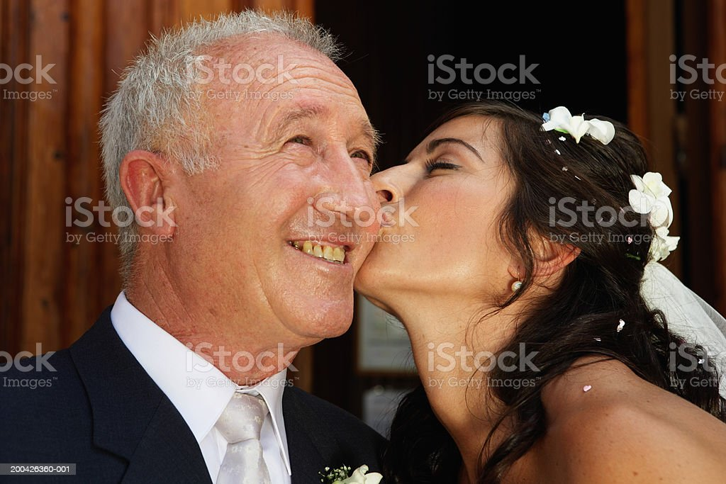 Bride kissing father on cheek, close-up stock photo