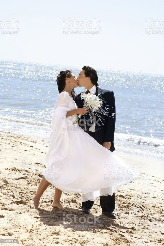 Bride kissing groom at the beach royalty-free stock photo