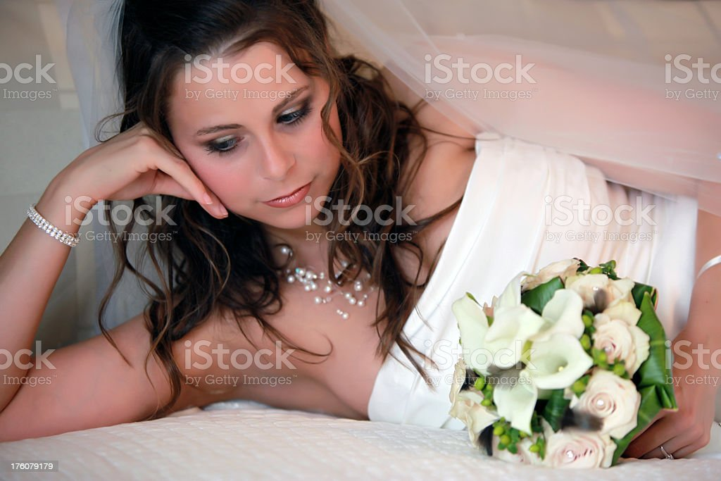 Bride laying on a bed on wedding day royalty-free stock photo